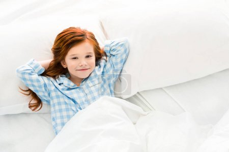 adorable little child in pajamas lying in bed and smiling at camera