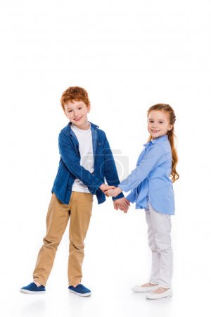beautiful redhead siblings holding hands and smiling at camera isolated on white