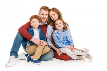 beautiful happy redhead family with two kids sitting together and smiling at camera isolated on white