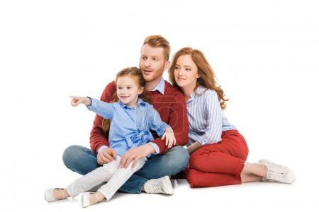 beautiful redhead family with one child sitting together and looking away isolated on white