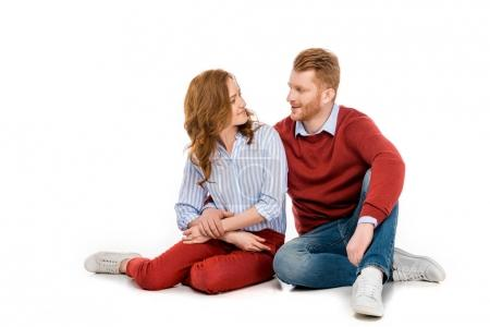 beautiful happy redhead couple sitting together and smiling each other isolated on white