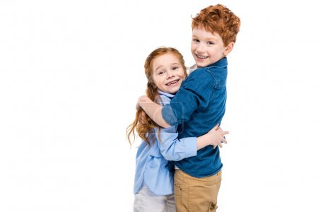 beautiful redhead brother and sister hugging and smiling at camera isolated on white