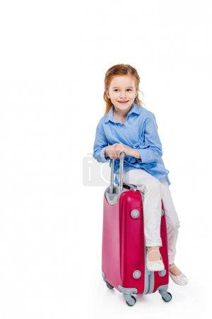 adorable happy child sitting on suitcase isolated on white