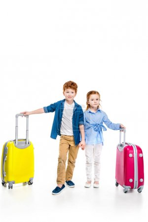 cute redhead children holding hands while standing with suitcases isolated on white