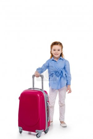 cute little child standing with suitcase and smiling at camera isolated on white