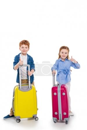 adorable smiling redhead kids standing with suitcases and showing thumbs up isolated on white