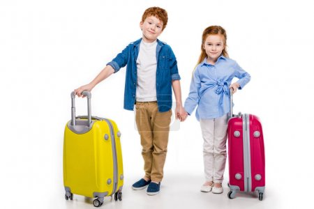 cute little kids holding hands while standing with suitcases and smiling at camera isolated on white