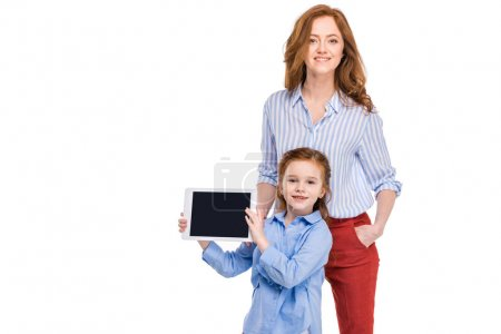 happy mother and daughter with digital tablet smiling at camera isolated on white