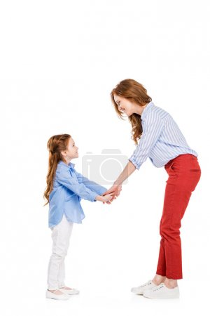 side view of happy redhead mother and daughter holding hands and smiling each other isolated on white