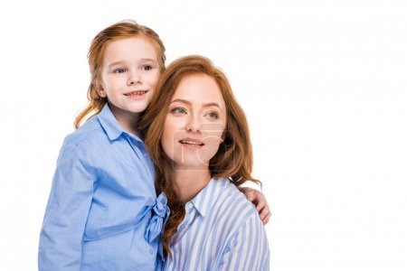 beautiful redhead mother and daughter smiling and looking away isolated on white