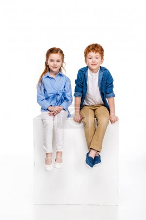 adorable redhead kids sitting together and smiling at camera isolated on white
