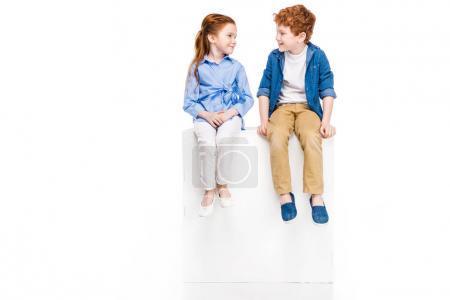Photo pour Adorables petits enfants assis sur cube blanc et se souriant isolés sur blanc - image libre de droit
