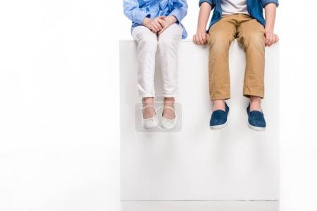 cropped shot of children sitting on white cube isolated on white