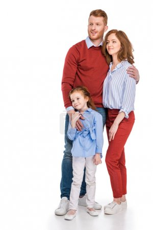 happy redhead family with one kid standing together and looking away isolated on white
