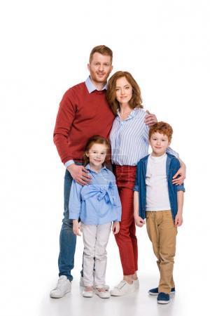 heureux rousse famille avec deux enfants debout ensemble et souriant à la caméra isolé sur blanc