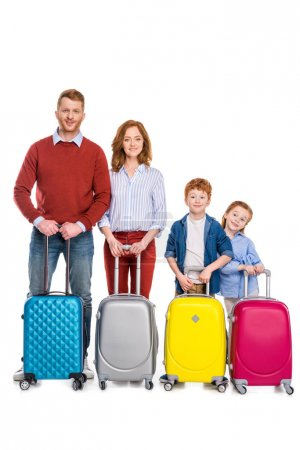 Photo for Happy redhead family standing with colorful suitcases and smiling at camera isolated on white - Royalty Free Image