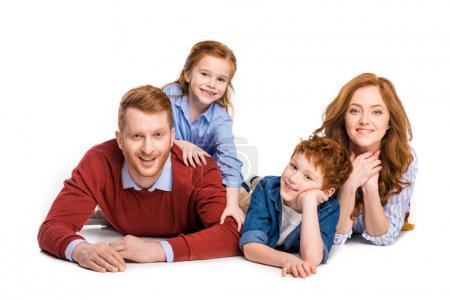 happy red haired family with two kids lying together and smiling at camera isolated on white