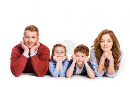 happy redhead family lying together and smiling at camera isolated on white