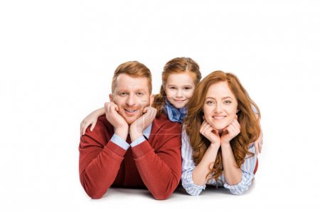 happy parents with adorable little daughter lying together and smiling at camera isolated on white