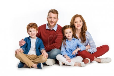happy family with two kids sitting together and smiling at camera isolated on white
