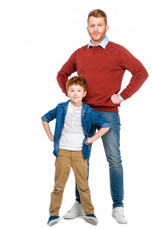 redhead father and son standing with hands on waist and looking at camera isolated on white