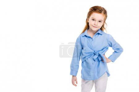 beautiful little child standing with hand on waist and smiling at camera isolated on white