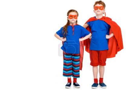 super children in masks and cloaks standing with hands on waist and looking at camera isolated on white