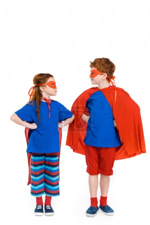 super kids in masks and cloaks standing with hands on waist and looking at each other isolated on white