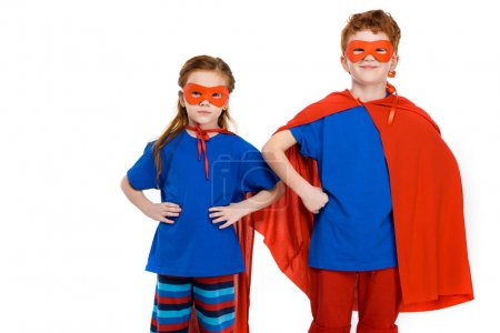 super kids in masks and cloaks standing with hands on waist and looking at camera isolated on white
