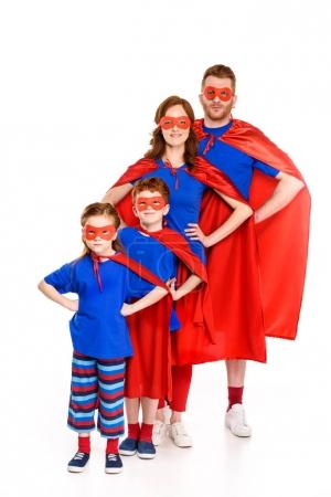 super family in masks and cloaks standing with hands on waist and smiling at camera isolated on white