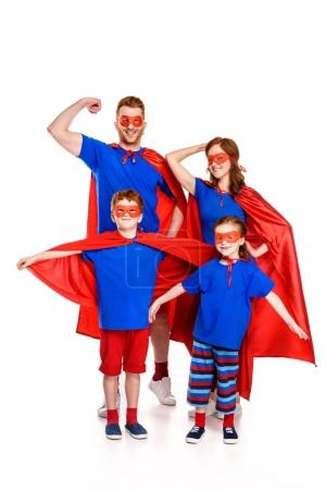 Photo for Super family in masks and cloaks standing together and smiling at camera isolated on white - Royalty Free Image