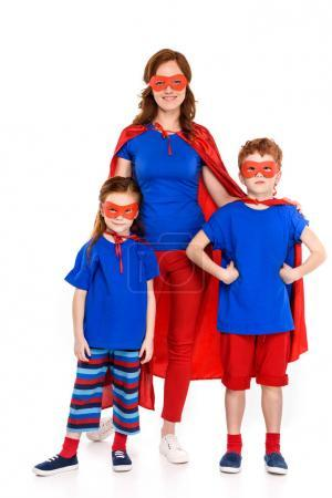 Photo for Happy mother with cute little kids in superhero costumes standing together and smiling at camera isolated on white - Royalty Free Image