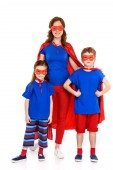 happy mother with cute little kids in superhero costumes standing together and smiling at camera isolated on white