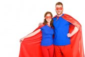 happy couple of superheroes standing together and smiling at camera isolated on white