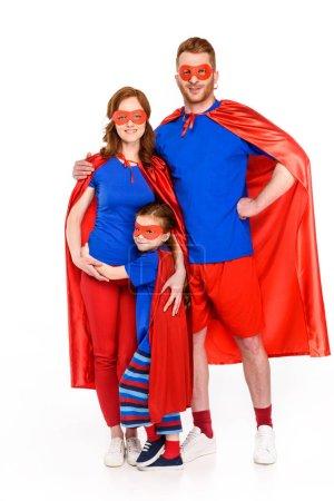 Photo pour Super famille masques et capes rassemblés et souriant à la caméra isolé sur blanc - image libre de droit