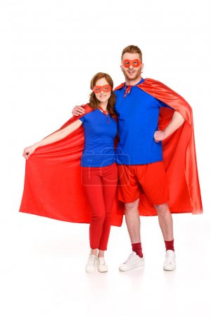 Photo for Super couple in masks and cloaks standing together and smiling at camera isolated on white - Royalty Free Image