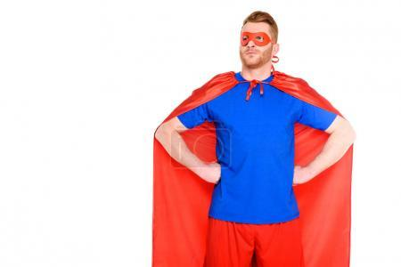 handsome man in superhero costume standing with hands on waist and looking away isolated on white
