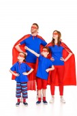 confident family of superheroes in masks and cloaks standing with hands on waist and looking away isolated on white