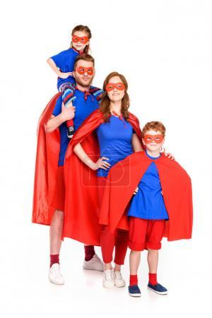 family of superheroes in masks and cloaks smiling at camera isolated on white