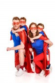 happy super parents piggybacking adorable smiling kids in masks and cloaks isolated on white