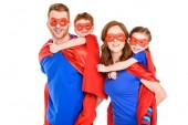 super parents piggybacking happy kids in masks and cloaks isolated on white