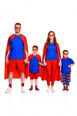 Foto de Familia super feliz en máscaras y mantos cogidos de la mano y sonriendo a cámara aislada en blanco - Imagen libre de derechos
