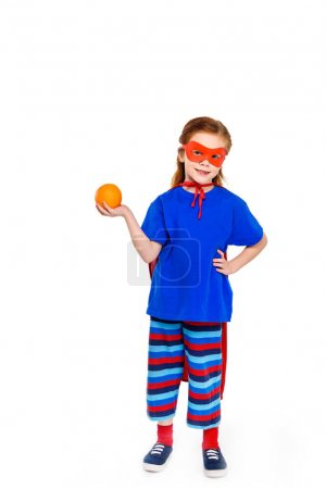 adorable child in superhero costume holding orange and smiling at camera isolated on white