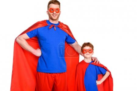 super father and son in masks and cloaks standing together and smiling at camera isolated on white