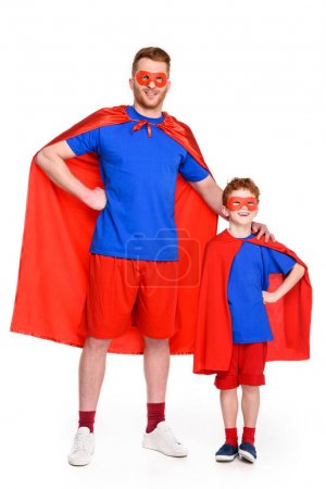 father and son in superhero costumes standing together and smiling at camera isolated on white