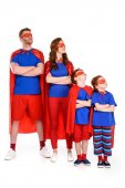 family of superheroes in costumes standing with crossed arms and looking away isolated on white