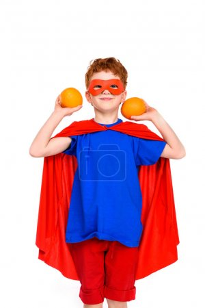 happy child in superhero costume holding oranges and smiling at camera isolated on white