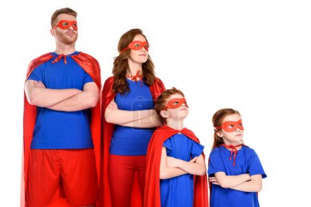 Photo for Confident family of superheroes in costumes standing with crossed arms and looking away isolated on white - Royalty Free Image