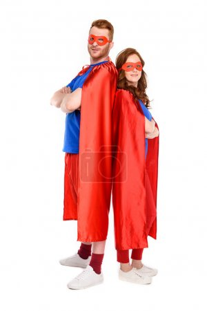 Photo for Full length view of couple of superheroes in costumes standing with crossed arms and looking at camera isolated on white - Royalty Free Image