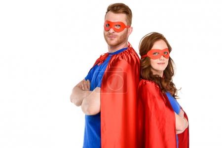 Photo for Couple of superheroes in costumes standing with crossed arms and looking at camera isolated on white - Royalty Free Image